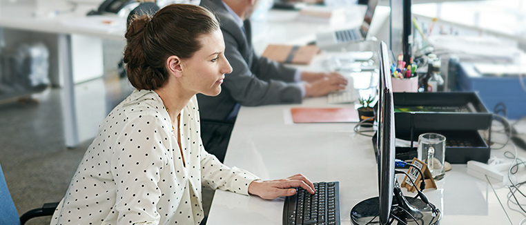 Businesswoman in office working on her computer